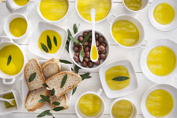 Dishes with extra virgin olive oil, bread and olive leaves