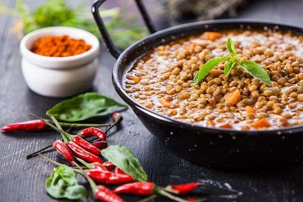 Lentil stew in black pan on wooden table decorated with paprika bowl and cayenne.