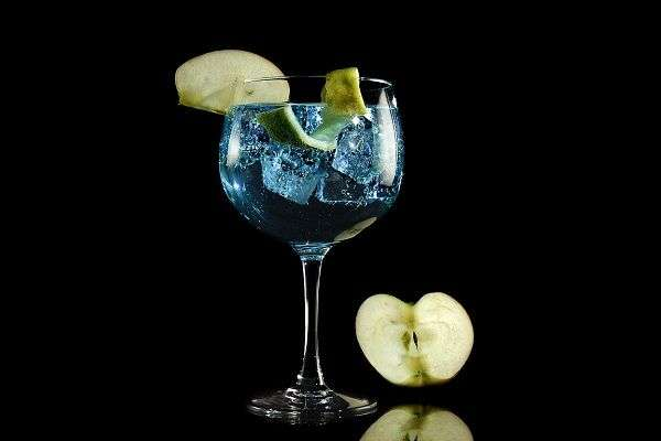 Blue gin tonic with green apple with black background