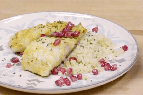 White plate with frets with codfish marinated with couscous and pomegranate