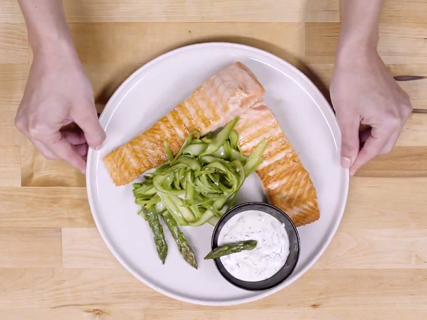 Hands showing white plate with grilled salmon, asparagus and yogurt sauce in a black bowl decorated with a green asparagus.