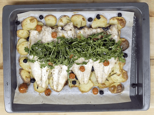 Baking tray on wooden table with sea bass with rosemary, black olives and cherry tomatoes on potato base