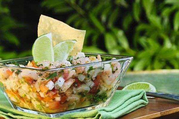 92/5000 Shrimp and octopus ceviche in transparent glass vase on green tablecloth.