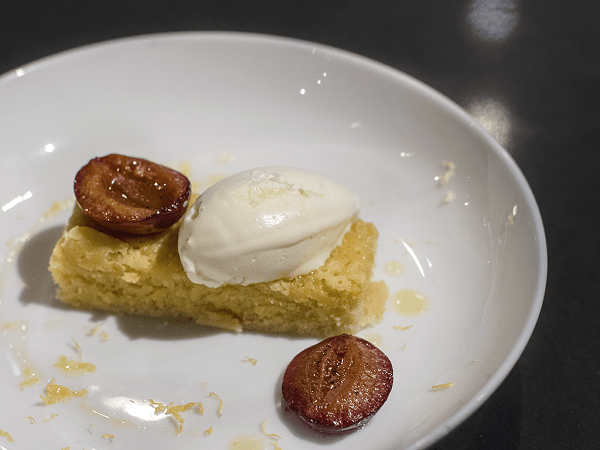 Olive oil and almond cake on white plate on black table