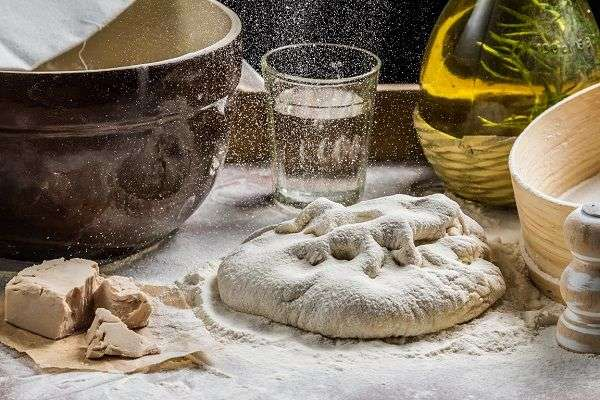 Pizza dough, yeast, bottle of oil, salt on table covered with flour