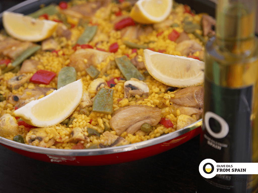 Paella pan with vegetables paella on table with bottle of extra virgin olive oil from Spain